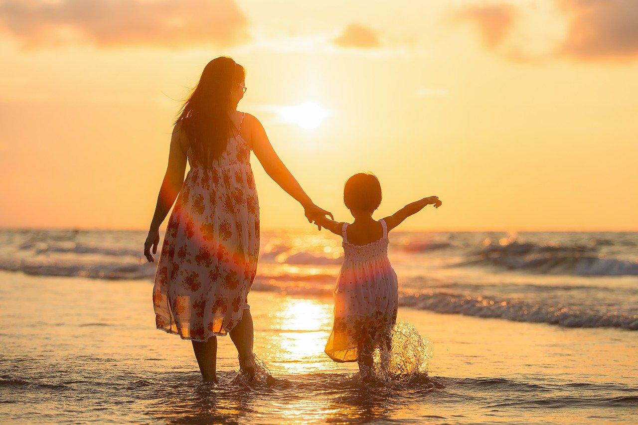 woman child walking on beach