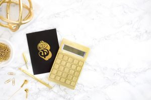 Gold calculator on marble desk